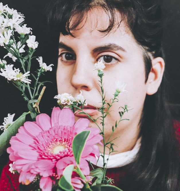 Image featuring a young disabled woman holding flowers