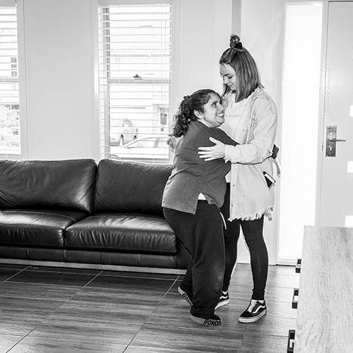 Civic Assisted Living staff hugging a client
