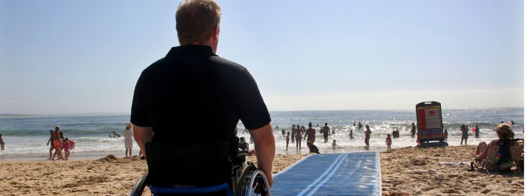 physically disabled man sitting in his wheel chair at the beach.